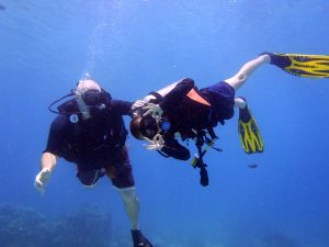 Family in action, father and son dive together scuba diving phuket